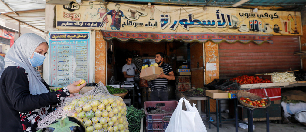 A woman buys vegetables from a cafe transformed into a fruit and vegetable shop, as cafes have been closed following the outbreak of the coronavirus disease (COVID-19), in Cairo, Egypt June 2, 2020. Picture taken June 2, 2020. REUTERS/Mohamed Abd El Ghany - RC245H9D5UO8