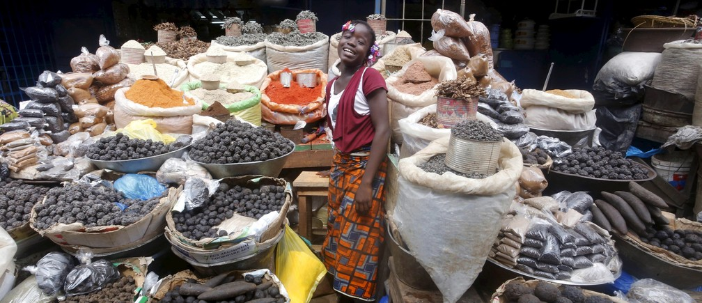 A girl smiles in between spices at Adjame's market in Abidjan, Ivory Coast, October 2, 2015.