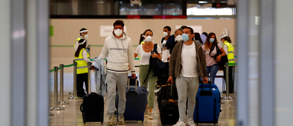 Pasajeros, con máscaras protectoras, caminan a su llegada desde París al aeropuerto Adolfo Suárez Barajas mientras España reabre sus fronteras a la mayoría de los visitantes europeos después del cierre del coronavirus, en Madrid, España, el 21 de junio de 2020.