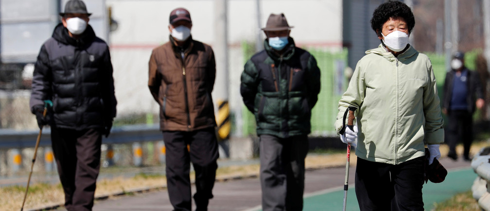 People wearing protective face masks following an outbreak of coronavirus disease (COVID-19), follow a trail in Cheongdo county, which has been designated as a 'special care zone' since the coronavirus outbreak, near Daegu in North Gyeongsang Province, South Korea, March 11, 2020.   REUTERS/Kim Kyung-Hoon - RC2MHF9YIYRK