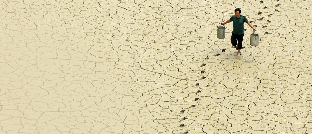 Picture of man walking across drought-stricken landscape carrying water pails
