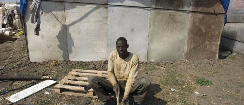 An African immigrant sits by his shack in a makeshift camp in the countryside near the village of Rignano Garganico, southern Italy, September 23, 2009.