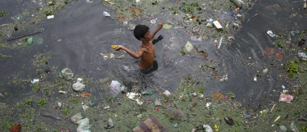 A boy throws a banana after collecting it from the polluted waters of river Sabarmati, in the western Indian city of Ahmedabad July 18, 2013.