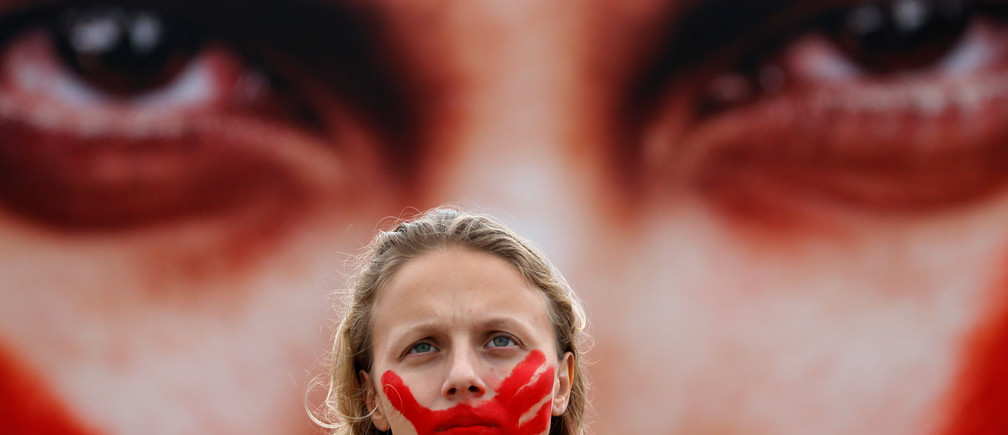 An activist poses for picture in front a photo from Brazilian photographer Marcio Freitas, during a protest by non-governmental organization (NGO) Rio de Paz (Rio of Peace) against rape and violence against women on Copacabana beach in Rio de Janeiro, Brazil, June 6, 2016. REUTERS/Sergio Moraes      EDITORIAL USE ONLY. - RTSG8Y3