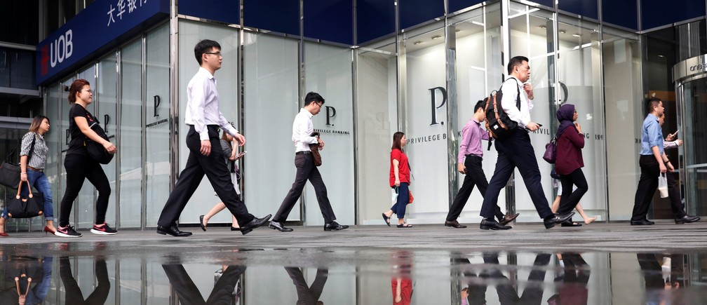 Office workers pass a UOB bank branch in Singapore's central business district April 27, 2017.