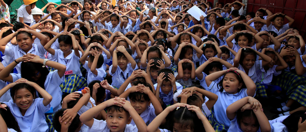 Students use their hands to cover their heads during an earthquake drill at the Baclaran Elementary School Unit-1 in Paranaque city, metro Manila, Philippines
