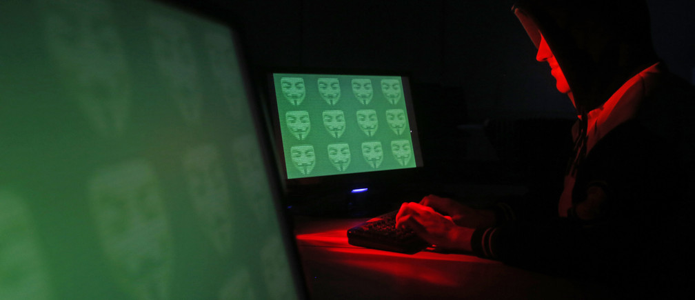 Man poses in front of on a display showing the word 'cyber' in binary code, in this picture illustration taken in Zenica December 27, 2014. A previously undisclosed hacking campaign against military targets in Israel and Europe is probably backed by a country that misused security-testing software to cover its tracks and enhance its capability, researchers said. Picture taken December 27, 2014. REUTERS/Dado Ruvic (BOSNIA AND HERZEGOVINA - Tags: SCIENCE TECHNOLOGY CRIME LAW TPX IMAGES OF THE DAY) - GM1EACS1HDA01