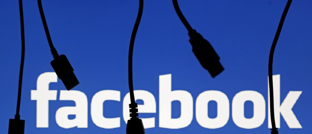 Electronic cables are silhouetted next to the logo of Facebook in this September 23, 2014 illustration photo in Sarajevo.   REUTERS/Dado Ruvic (BOSNIA AND HERZEGOVINA  - Tags: BUSINESS TELECOMS)   - LR1EA9O0V25E7