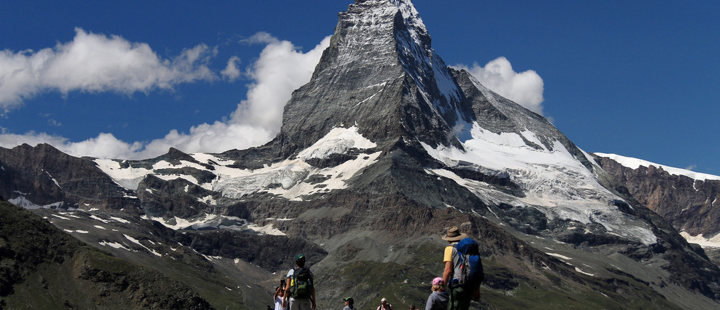 People hike as they enjoy the view of Matterhorn mountain seen at the background in Zermatt, Switzerland July 30, 2019. Picture taken July 30, 2019. REUTERS/Catherine Muzolf - RC169081E900