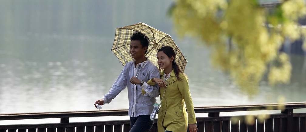A couple walks near a seasonal flower known as Ngu War in Myanmar as they celebrate Thingyan, the country's New Year Water Festival, in Yangon April 16, 2013.