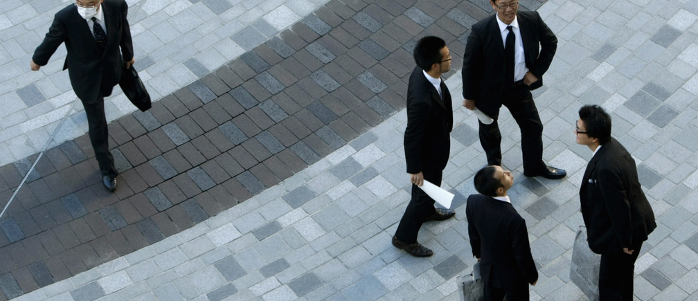 Businessmen stand on a street in Tokyo November 13, 2007.
