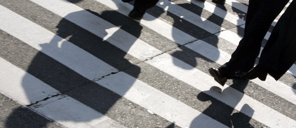 Businessmen cast shadows as they cross a street in Tokyo's Marunouchi district
