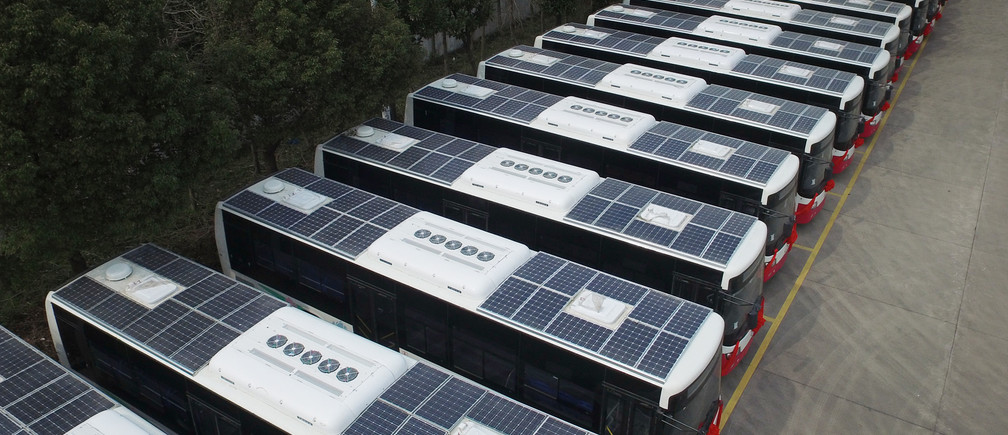 Buses with solar panels installed on their roofs to save electricity are seen in a parking lot in Hangzhou, Jiangsu Province, China, March 17, 2016.