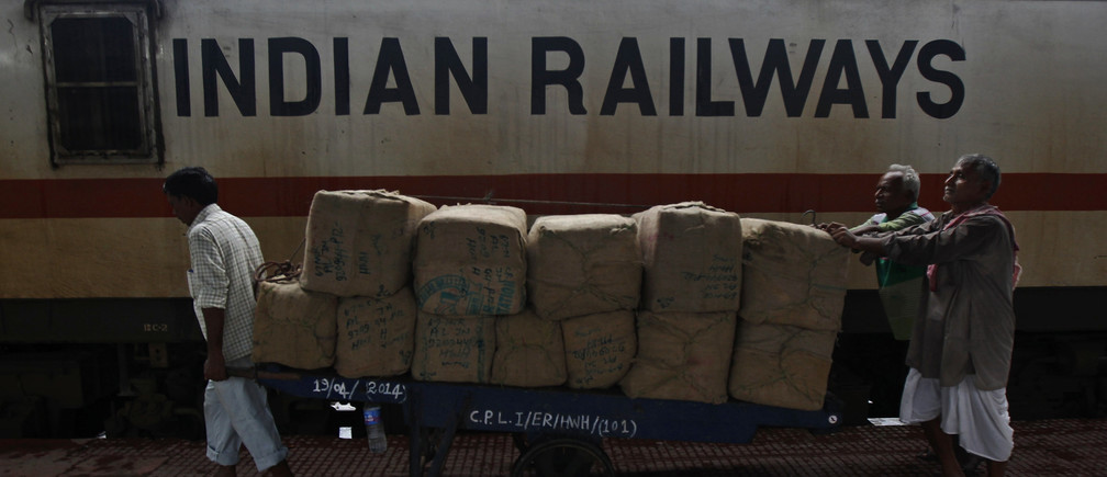 Porters transport goods on a hand-pulled trolley to load onto a train at a railway station in Kolkata July 8, 2014. Indian Prime Minister Narendra Modi's government disappointed markets with its first major economic policy statement on Tuesday, promising to seek foreign and private funding for the railways but giving no details of how it would lure investors. India's state-owned railways are the fourth-largest in the world. They have suffered from years of low investment and populist policies that have kept fares low. REUTERS/Rupak De Chowdhuri (INDIA - Tags: TRANSPORT BUSINESS POLITICS) - RTR3XN4H
