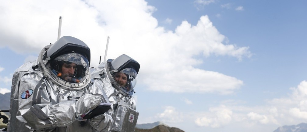 Inigo Munoz Elorza of Spain works together with Stefan Dobrovolny of Austria (R) during a simulated Mars mission on Tyrolean glaciers in Kaunertal, Austria, August 7, 2015. The Austrian Space Forum is sending some of its researchers to practice weight-less walking in spacesuits on a glacier which resembles the terrain on Mars. REUTERS/Dominic Ebenbichler  - RTX1NH0P