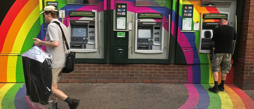 A customer withdraws money from an ATM at a Toronto-Dominion (TD) bank branch adorned in colours of the Pride rainbow flag symbolizing gay rights, in downtown Toronto, Ontario, Canada June 13, 2017. Picture taken June 13, 2017