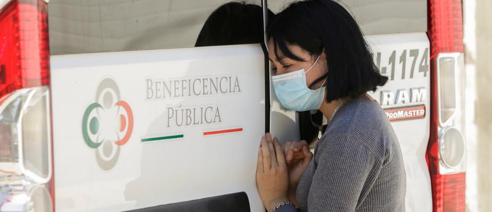 Una mujer se inclina en la puerta de una ambulancia que transporta el cuerpo de un hombre que murió de la enfermedad coronavirus (COVID-19) antes de ser trasladado a un hospital, en Ciudad Juárez, México, el 26 de mayo de 2020.