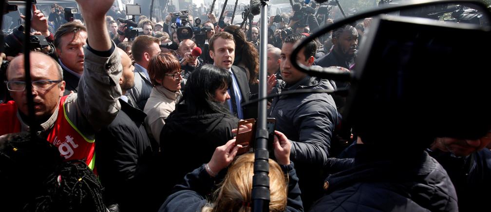 Emmanuel Macron (C), head of the political movement En Marche !, or Onwards !, and candidate for the 2017 French presidential election, is surrounded by journalists as he arrives to meet Whirlpool employees in front of the company plant in Amiens, France, April 26, 2017.  REUTERS/Pascal Rossignol - RC1C0CBA4350