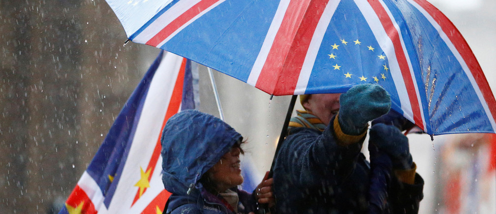 Anti-Brexit protesters shelter from the rain outside the Houses of Parliament, after Prime Minister Theresa May's Brexit deal was rejected, in London, Britain, January 16, 2019. REUTERS/Henry Nicholls - RC1197B73EC0