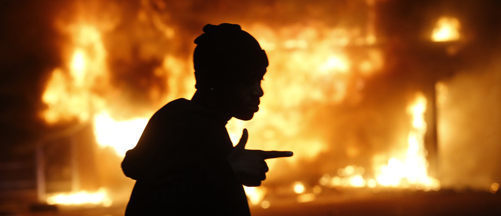 A man walks past a burning building during rioting after a grand jury returned no indictment in the shooting of Michael Brown in Ferguson, Missouri, early November 25, 2014. Gunshots were heard and bottles were thrown as anger rippled through a crowd outside the Ferguson Police Department in suburban St. Louis after authorities on Monday announced that a grand jury voted not to indict a white officer in the August shooting death of an unarmed black teen