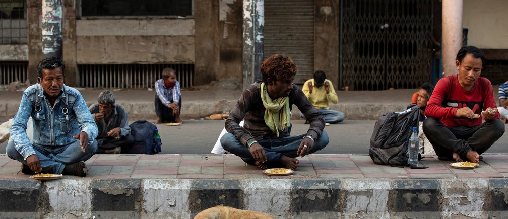 Daily wage labourers and homeless people eat food distibuted by a non-governmental organisation during an extended nationwide lockdown to slow the spread of the coronavirus disease (COVID-19) in New Delhi, India, April 28, 2020. REUTERS/Danish Siddiqui - RC2QDG90ZBUV