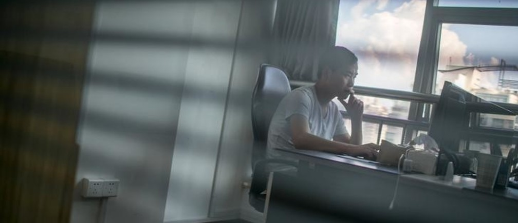 Zhang Xiongjie looks at a computer screen as he works at his office in Hangzhou, Zhejiang province, July 27, 2015. A decade ago Zhang was a teenage infantryman patrolling China's bleak border with North Korea. Now he stays in swanky hotels and drives a Mercedes Benz CLS - a remarkable rags-to-riches journey achieved in part by dominating one of the most obscure corners of China's unruly financial markets: egg futures. Picture taken July 27, 2015. To match Feature CHINA-MARKETS/EGGFUTURES REUTERS/Chance Chan