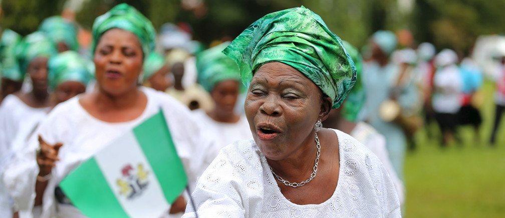 A woman raises the Nigerian flag as she participates in a parade to commemorate Nigeria's 55th Independence Day in Lagos, October 1, 2015.  REUTERS/Akintunde Akinleye - GF10000228741