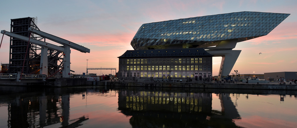The sun rises behind the new headquarters for the Antwerp Port Authority on the Kattendijk dock, the Port House, a monumental design by Zaha Hadid Architects in Antwerp, Belgium September 22, 2016. Reuters/Eric Vidal - D1BEUCSRSFAA