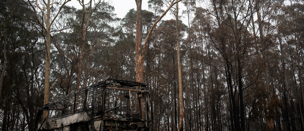 A destroyed bus is seen next to burnt bushland in the village of Mogo, Australia, January 8, 2020. REUTERS/Alkis Konstantinidis     TPX IMAGES OF THE DAY - RC2HBE9RX45S
