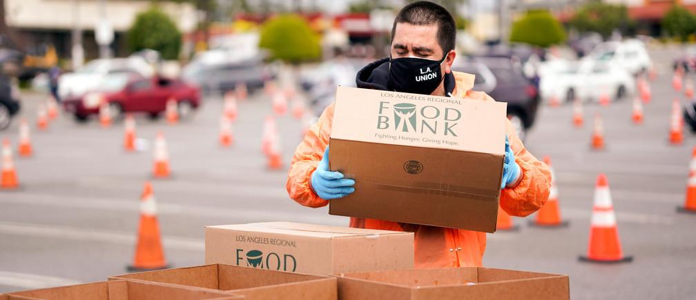 Un voluntario de la Federación del Trabajo del Condado de Los Ángeles, AFL-CIO, reparte cajas de comida a los trabajadores de LAX en el aparcamiento de El Foro durante el brote de la enfermedad coronavirus (COVID-19), en Inglewood, California, EE.UU., el 10 de abril de 2020.