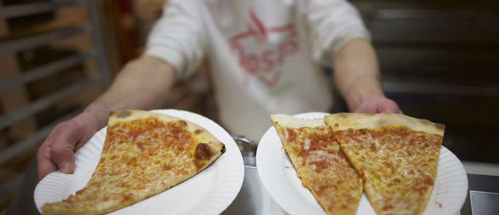 Rosa's Fresh Pizza owner Mason Wartman, a former Wall Street equity researcher, reaches to heat slices of pizza in Philadelphia, Pennsylvania January 10, 2015. The $1 a slice pizzeria, which opened in December 2013, has provided 8,500 slices of pizza to the homeless in the last 9 months.  With a 'pay-it-forward' approach, customers donate dollars to feed those in need.  REUTERS/Mark Makela (UNITED STATES - Tags: FOOD SOCIETY POVERTY) - RTR4KV7X