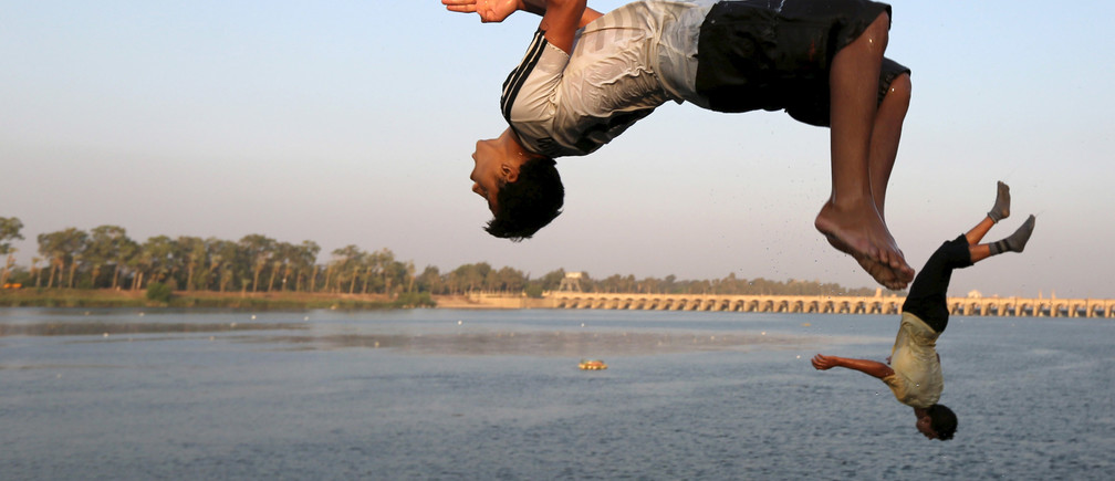 Boys jump into the river Nile during hot weather on the outskirts of Cairo, Egypt, August 12, 2015
