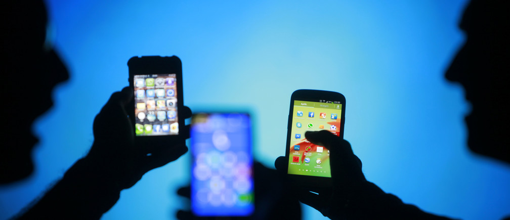 Men are silhouetted against a video screen as they pose with Samsung Galaxy S3, Nokia Lumia 820 and iPhone 4 smartphones (R-L) in this photo illustration taken in the central Bosnian town of Zenica, May 17, 2013. REUTERS/Dado Ruvic (BOSNIA AND HERZEGOVINA - Tags: BUSINESS TELECOMS) - RTXZQ6N