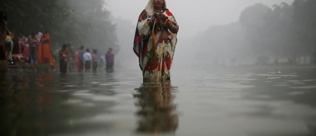 A Hindu devotee worships the Sun god amidst heavy smog at a pond during Chhath Puja in New Delhi, India November 6, 2016. REUTERS/Adnan Abidi
