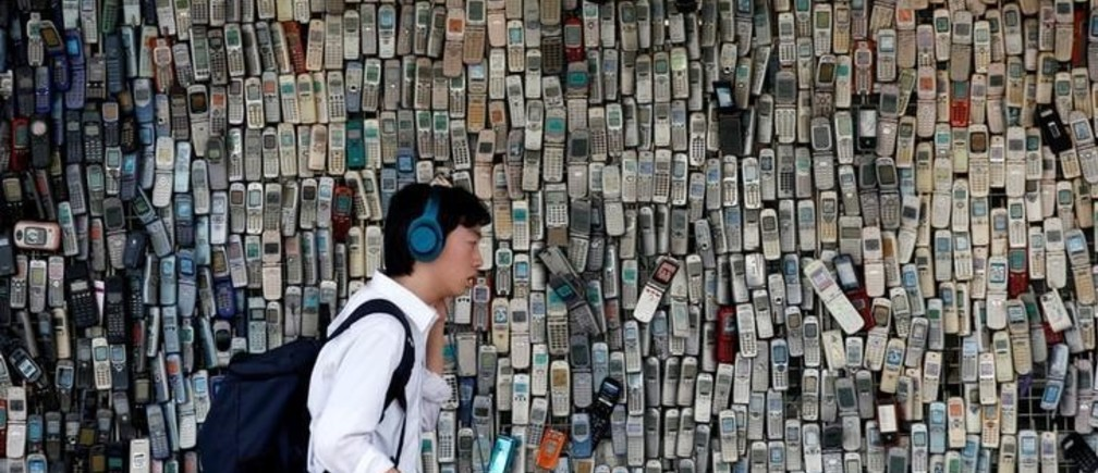 A man using a smartphone walks past an electronic shop's wall decorated with old cell phones which its owner Watanabe Masanao had collected over 20 years is pictured in Tokyo, Japan July 5, 2017. REUTERS/Kim Kyung-Hoon     TPX IMAGES OF THE DAY