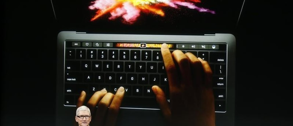 Apple CEO Tim Cook speaks under a graphic of the new MacBook Pro during an Apple media event in Cupertino, California, U.S. October 27, 2016.