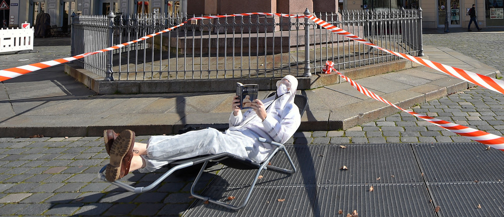 A man, wearing a protective mask, glasses and a suit is reading a book in the sun during a partial lockdown in Dresden, Germany, March 23, 2020, as the spread of the coronavirus disease (COVID-19) continues. REUTERS/Matthias Rietschel - UP1EG3N15H84Y