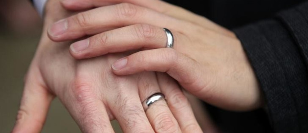 Bernie Liang (L), and Ryan Hamachek, show their rings after getting married outside Seattle City Hall in Seattle, Washington December 9, 2012. Washington made history last month as one of three U.S. states where marriage rights were extended to same-sex couples by popular vote, joining Maryland and Maine in passing ballot initiatives recognizing gay nuptials.  REUTERS/Cliff Despeaux (UNITED STATES - Tags: POLITICS SOCIETY)