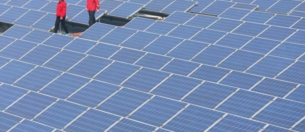 Workers walk past solar panels in Jimo, Shandong Province, China, April 21, 2016