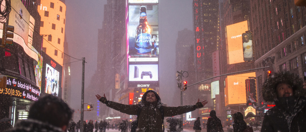 Shayan Oman, a visitor from Perth, Australia, poses for photos during a snow storm in New York's Times Square January 26, 2015. A massive blizzard slammed into the U.S. Northeast on Monday, canceling thousands of flights, curtailing mass transit and closing hundreds of schools, as officials warned that the storm could dump as much as 3 feet of snow on the region.  REUTERS/Adrees Latif  (UNITED STATES - Tags: ENVIRONMENT) - GM1EB1R0LZ801