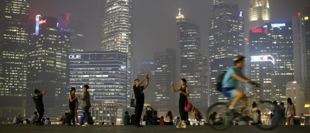 People take photos with the skyline of the central business district shrouded by haze in Singapore September 10, 2015. REUTERS/Edgar Su