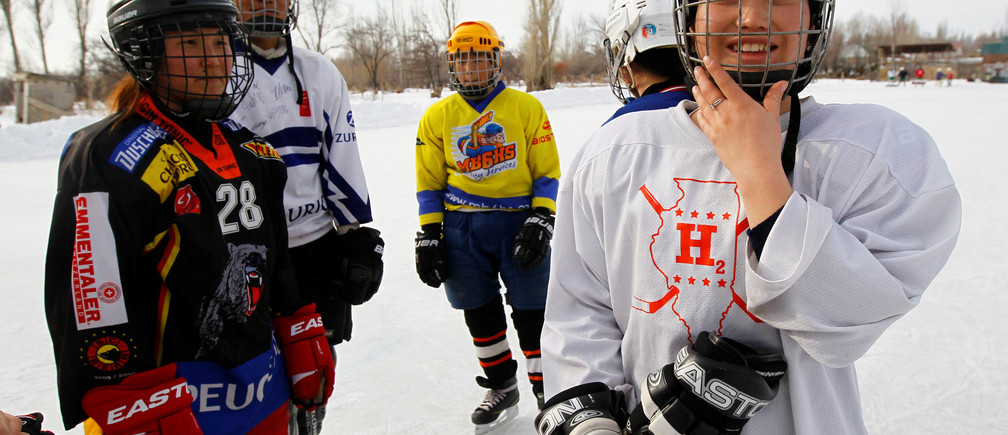 Members of Kyrgyzstan's first female hockey team are seen during a training session in the village of Otradnoye, Kyrgyzstan women men female male girls boys teenagers teens development gender gap parity equality diversity progress change femmine masuline woman man sex biology roles dynamic balance bias androgynous