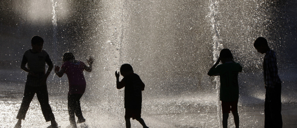 Jordanian boys cool off under a fountain during an unseasonal heat wave with temperatures reaching a high of 31 degrees Celsius (87 degrees Farenheit) in downtown Amman June 15, 2010.