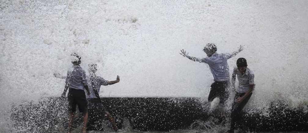 School boys get drenched in a large wave during high tide at a sea front in Mumbai July 14, 2014. Weak rainfall in India since the start June, when the monsoon season began, has raised concerns of a first drought in five years, although weather experts are hopeful rains will revive in the next week. REUTERS/Danish Siddiqui (INDIA - Tags: SOCIETY ENVIRONMENT TPX IMAGES OF THE DAY)