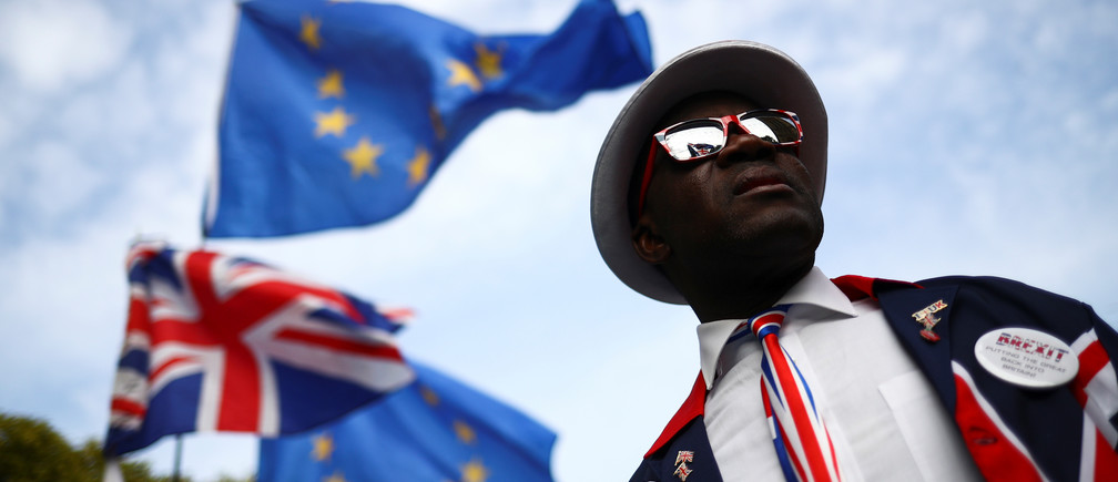 A pro-Brexit protester looks on as flags flutter outside the Houses of Parliament in London, Britain, October 28, 2019. REUTERS/Hannah McKay - RC16E8212210
