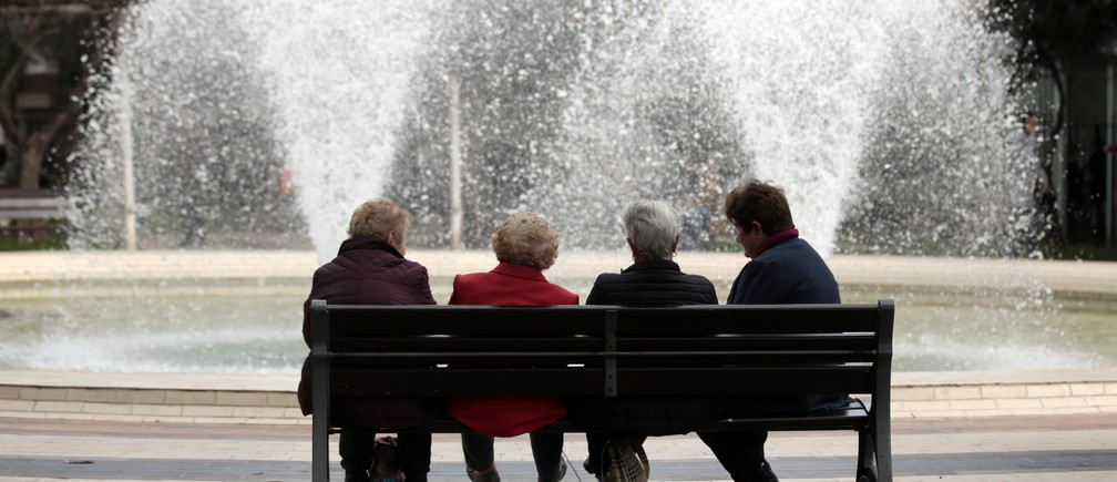 A group of elderly people sit on a bench near a fountain in a park in Nice, France, March 30, 2016.