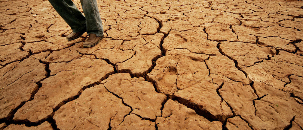 A Pakistani walks as cracks are seen at Rawal Lake in Islamabad, which is the main source of water supply to Rawalpindi, May 8, 2006. Pakistan is facing a possible drought as there are no signs of any significant rains in the country in the next couple of months, the country's top weatherman warned on Monday.  REUTERS/Mian Khursheed - GM1DSOEYPJAA