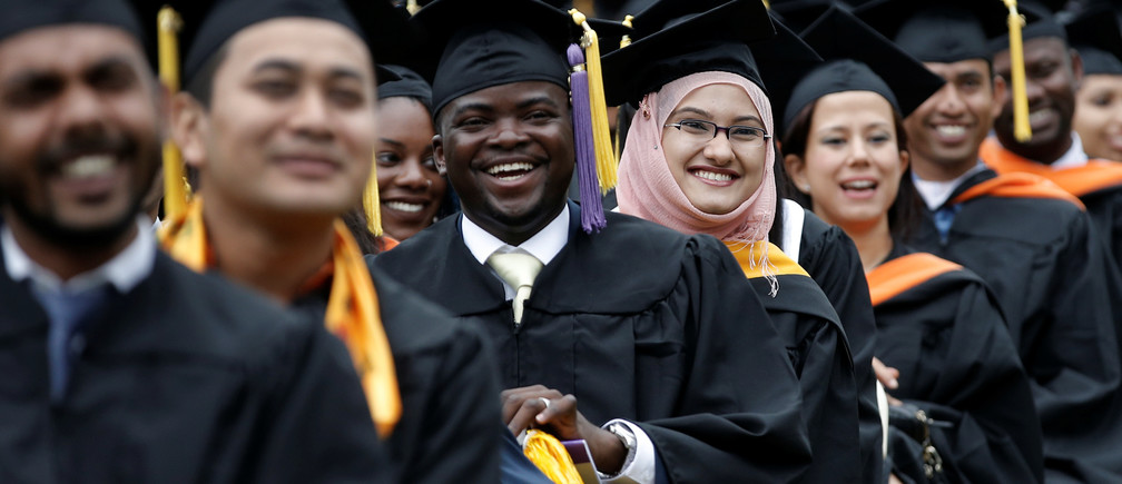Graduating students of the City College of New York sit together in their caps and gowns as they listen to U.S. first lady Michelle Obama's address during the College's commencement ceremony in the Harlem section of Manhattan, New York, U.S., June 3, 2016. REUTERS/Mike Segar - RTX2FKNP