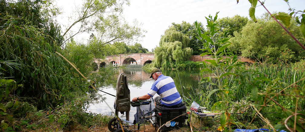 A man fishes on the River Thames in Sonning, Britain, a village where British Prime Minister Theresa May has a home, July 8, 2018. Picture taken July 8, 2018.    To match Special Report BRITAIN-EU/MAY  REUTERS/Henry Nicholls - RC16BF2AF830