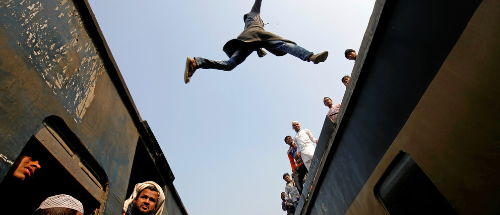 A commuter jumps between trains upon arrival at a station, to attend Akheri Munajat, the final supplication during Biswa Ijtema in Tongi, on the outskirts of Dhaka January 15, 2017. REUTERS/Mohammad Ponir Hossain TPX IMAGES OF THE DAY - RC1D6738EC20